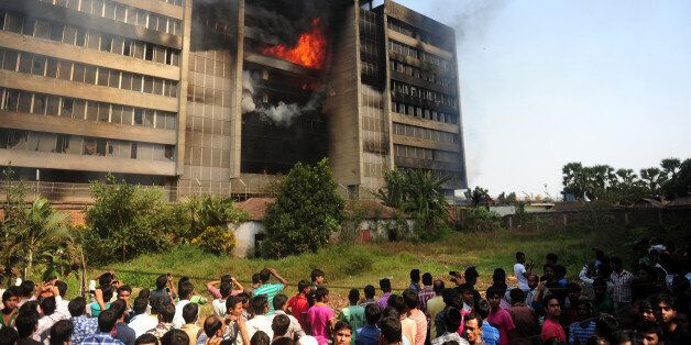 Bangladeshi bystanders watch as smoke and flames billow from a burning garment factory in the key garment manufacturing hub o