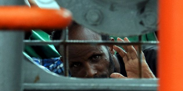 A migrant waits to disembark from the Norwegian cargo ship Siem Pilot after they were rescued in the...