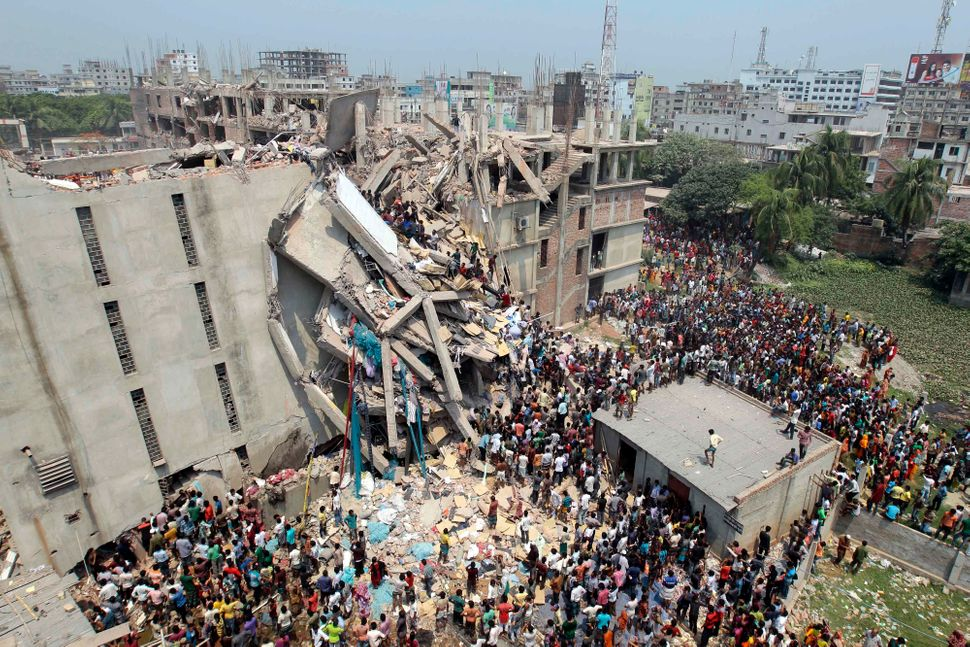 People and rescuers gather after an eight-story building housing several garment factories collapsed. 1,129 people died and m