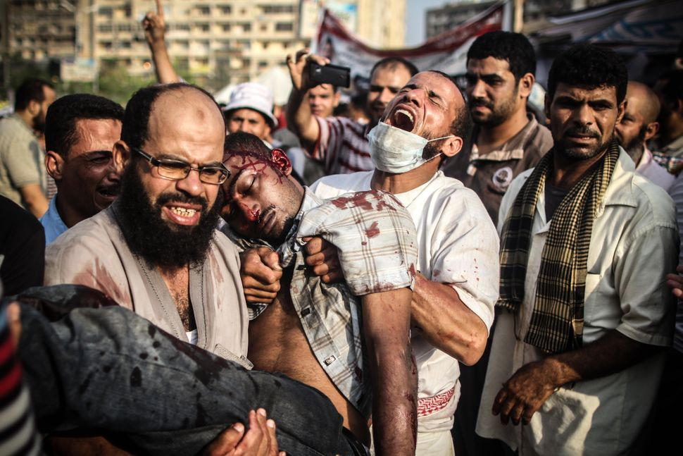 Pro-Morsi protesters in Rabaa Square carry a man shot during clashes with police. On July 3, President Mohamed Morsi — who wa
