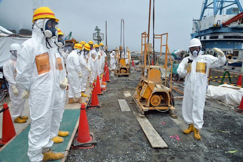 Local government officials and nuclear experts inspect a construction site to prevent the seepage of contamination water into