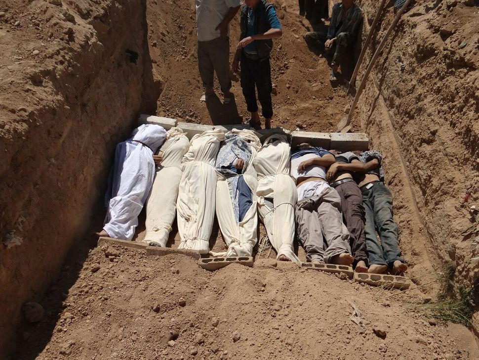Several bodies are buried in a suburb of Damascus, Syria, during a funeral. During Syria's civil war, several areas around Da