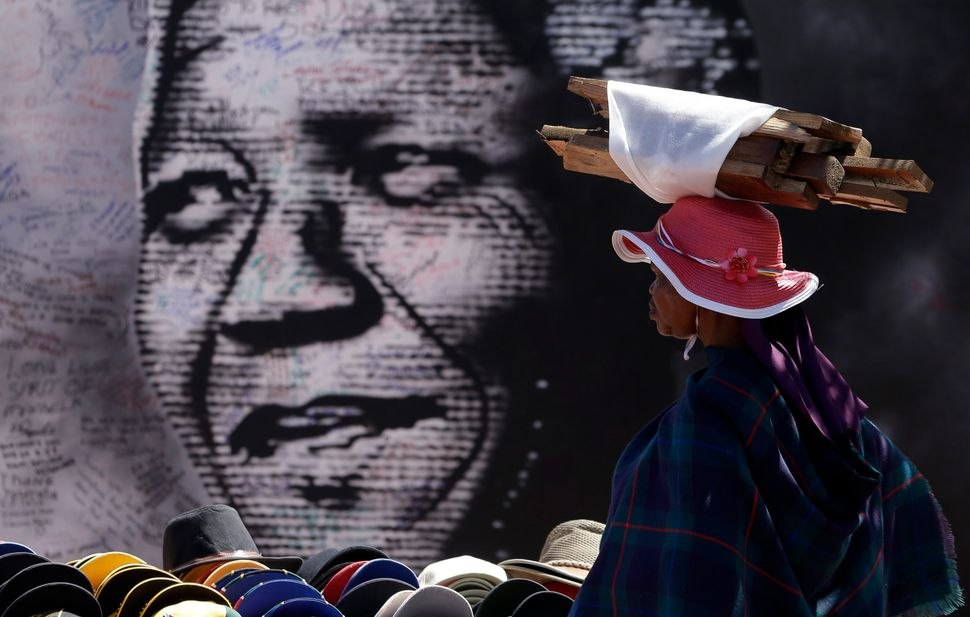 A woman carrying wood on her head takes a moment as she looks at former South African president Nelson Mandela's poster with