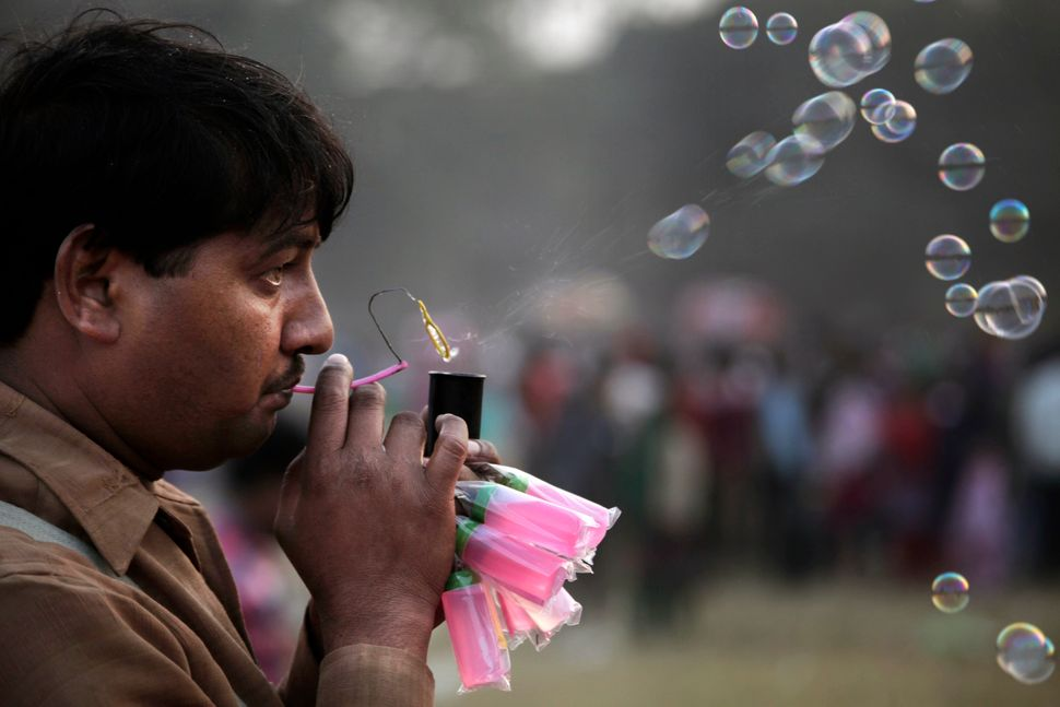 An Indian vendor blows soap bubbles to attract customers at a park in Kolkata, India, Wednesday, Jan. 1, 2014. Many people vi