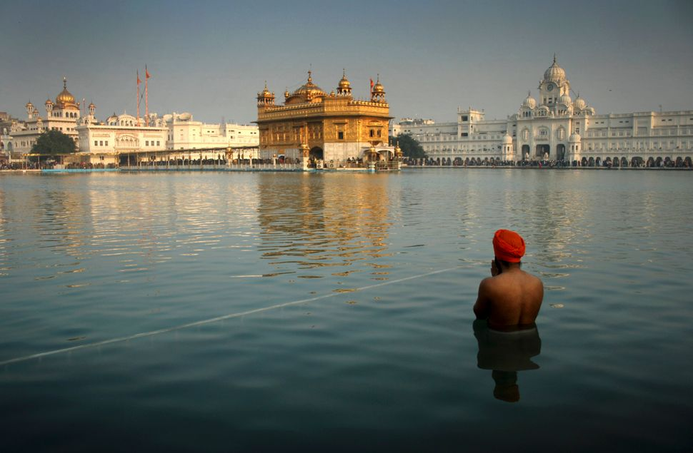 An Indian Sikh devotee takes a holy dip in the sacred pond at the Golden Temple in Amritsar, India, Wednesday, Jan. 1, 2014.