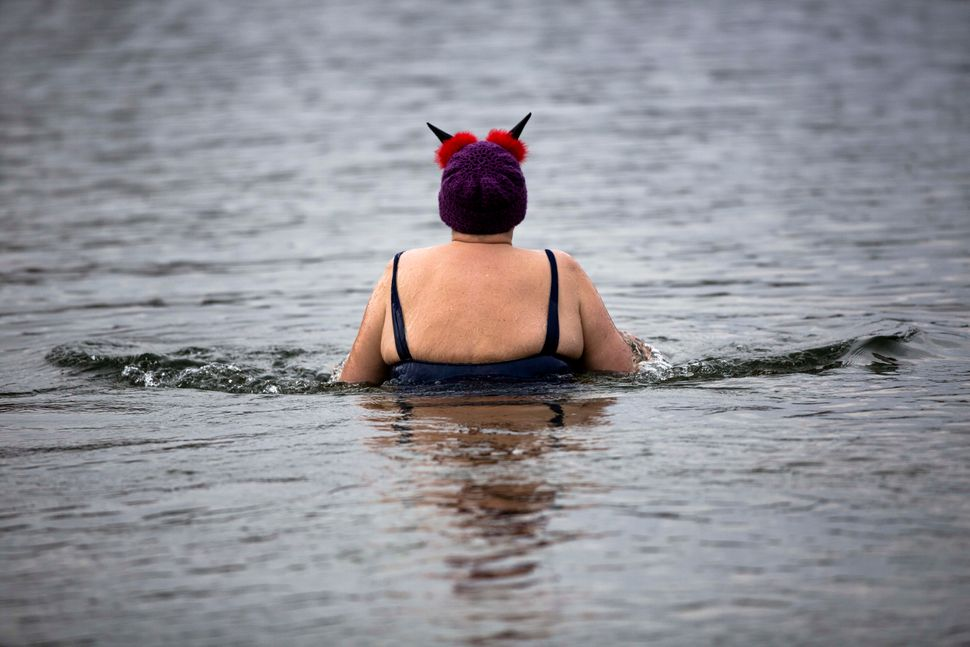 A woman with a New Years hat attends the annual New Year's swimming of the winter swimming club Berliner Seehunde (Berlin Sea