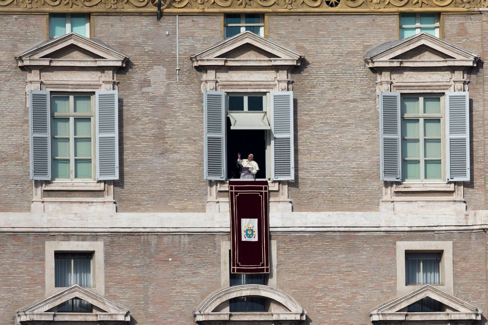 Pope Francis delivers his blessing during the Angelus noon prayer he celebrated from the window of his studio overlooking St.