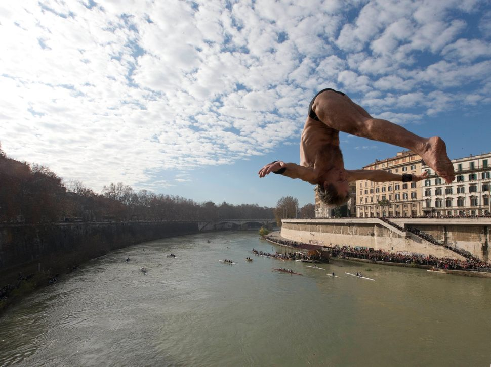 Italy's Marco Fois dives into the Tiber River from the 18 meter (59 feet) high Cavour Bridge in Rome, Wednesday, Jan. 1, 2014