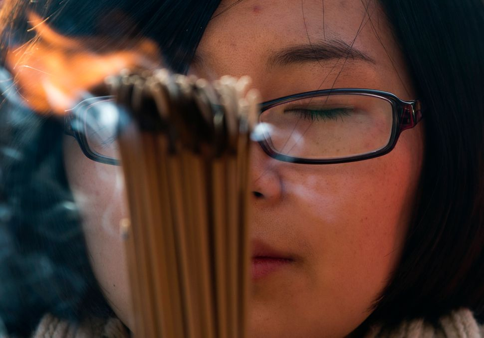 A Chinese woman prays on the first day of the New Year at the Yonghegong Lama Temple in Beijing Wednesday, Jan. 1, 2014. (AP