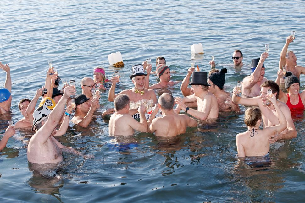People toast with champagne while swimming in the cold water, during the annual swim in the Lake of Geneva for celebrating th
