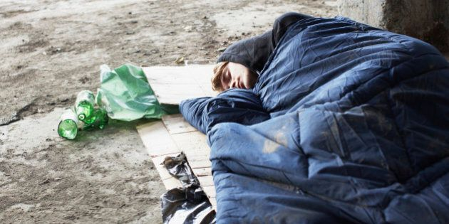 Homeless man sleeping in sleeping bag on
