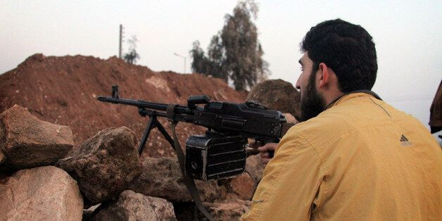 ALEPPO, SYRIA - JANUARY 4:  A man holds his rifle during clashes between the Free Syrian Army (FSA) and the Islamic State of