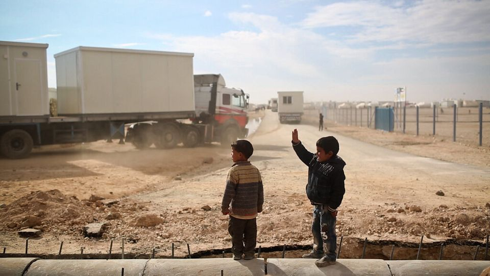 Two Syrian refugee boys watch a convoy of caravans arrive on Jan. 9, 2014, at Za'atari refugee camp in Jordan, which shelters