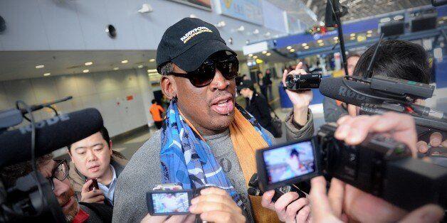 Former US NBA basketball player Dennis Rodman (C) speaks to members of the media as he makes his way through Beijing's intern