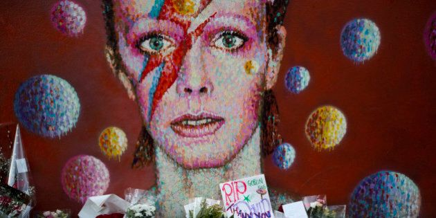 Tributes lie beneath a mural of British singer David Bowie by artist Jimmy C in Brixton, south London,...