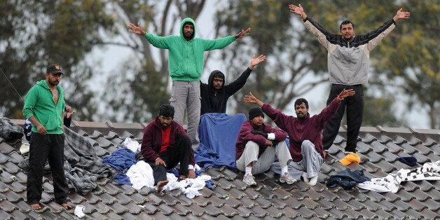 Sri Lankan asylum-seekers wave to supporters as they threaten to jump off the roof of the Villawood detention centre during a