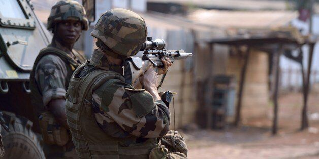 A French soldier part of the Sangaris operation forces aims rifle during a patrol at the 'Reconciliation crossroad' as uniden