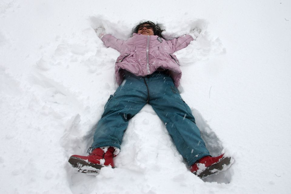 An Iranian girl plays in snow at the Dizin ski resort, 120 kms northwest of Tehran, on February 4, 2010. (ATTA KENARE/AFP/Get