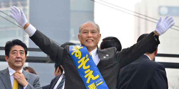 Japan's former health minister and current candidate for the Tokyo gubernatorial election Yoichi Masuzoe (C) waves during his