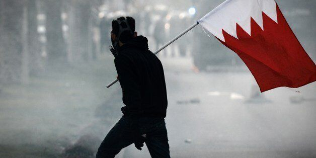 A Bahraini protester holds his national flag during clashes with riot police following the funeral of 20-year-old prisoner Fa