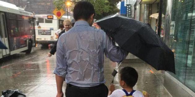 FOTO Un papà protegge il figlio dalla pioggia senza curarsi di bagnarsi. Lo scatto che ha fatto innamorare...