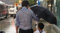 Protegge il figlio dalla pioggia senza curarsi di