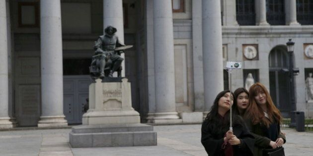 Tourists take a selfie beside a statue of Spanish painter Diego Velazquez outside El Prado Museum in...