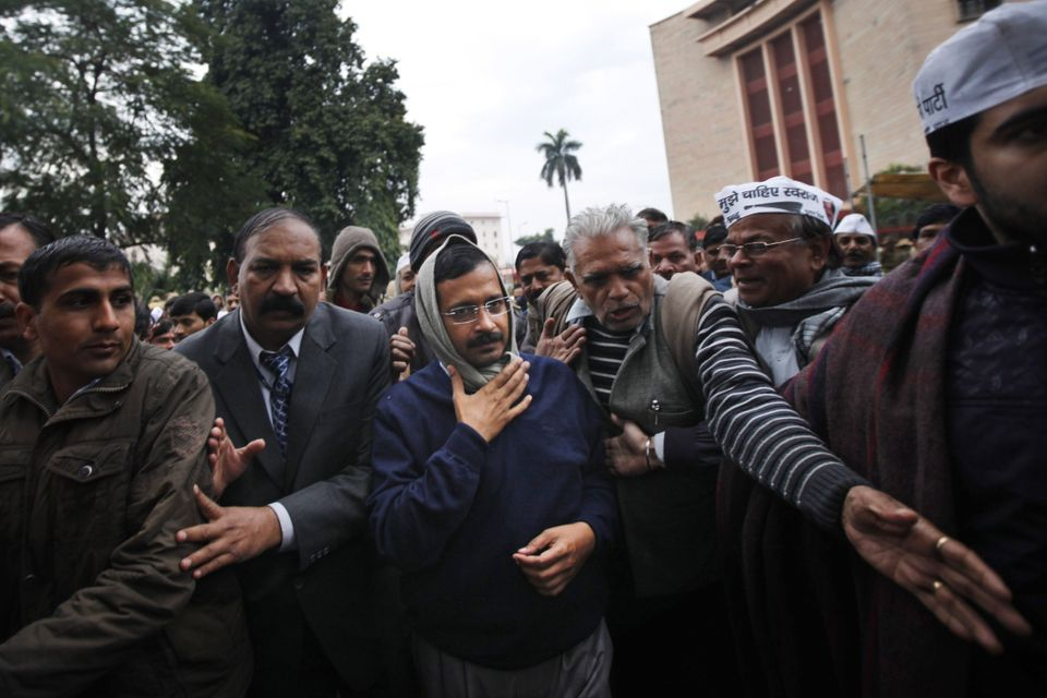 New Delhi Chief Minister Arvind Kejriwal, center, is escorted by supporters and security men during a demonstration against t