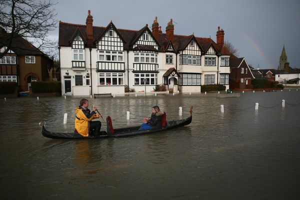 A couple promote the Piccola Venezia Italian restaurant by rowing their gondola through flood waters on February 12, 2014 in