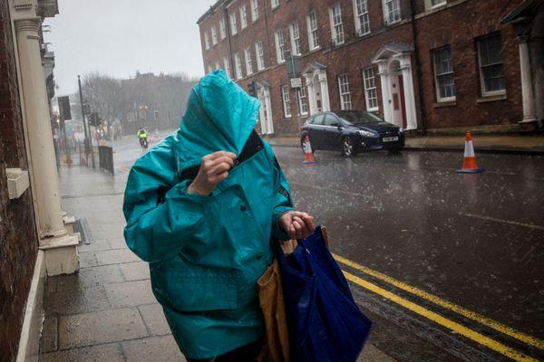 A woman walks along Bridge Street through heavy rain and hail on February 12, 2014 in Worcester, England. (Rob Stothard/Getty