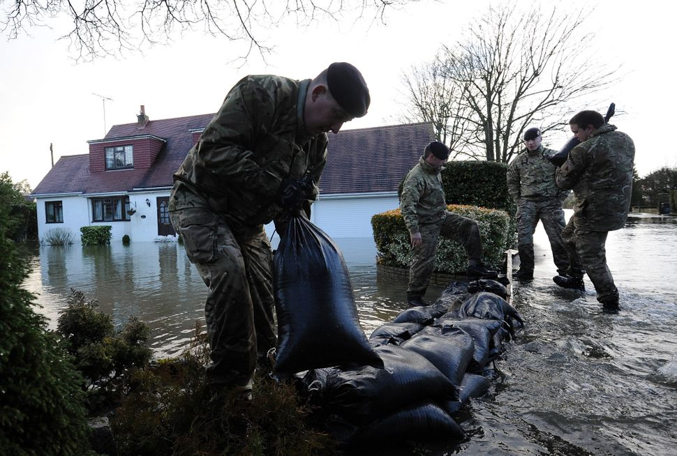 Soldiers attempt to protect a flooded property with sandbags in Wraysbury, west of London on February 12, 2014. (CARL COURT/A