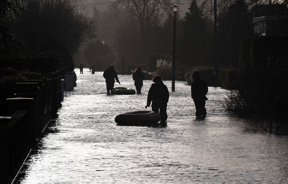 People walk along a flooded road in Wraysbury, west of London on February 12, 2014. (CARL COURT/AFP/Getty Images)