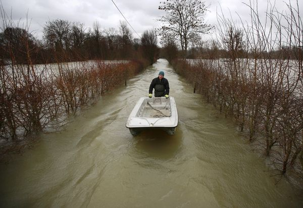 James Georgiadis pushes his boat along a flooded lane to his house on February 12, 2014 in Wraysbury, England. (Peter Macdiar