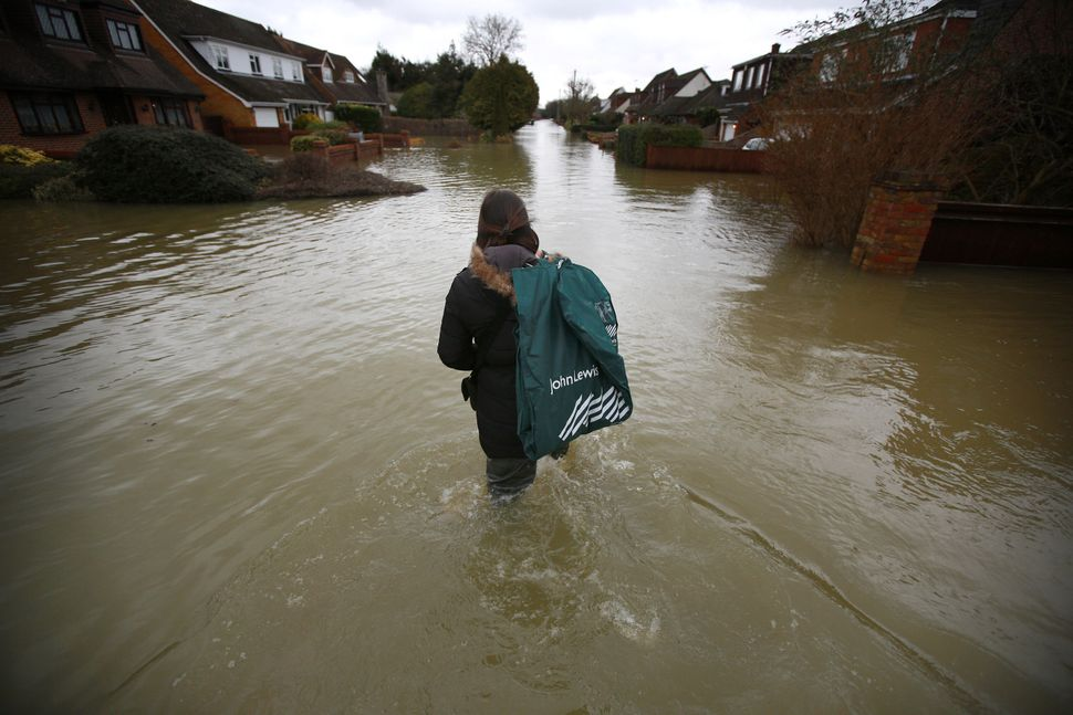 Kellie Evans makes her to work through flood water on February 12, 2014 in Wraysbury, England. (Peter Macdiarmid/Getty Images