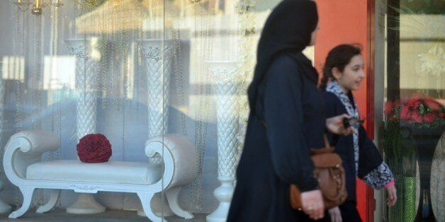 TO GO WITH AFP STORY BY ASSAD ABBOUD Saudi women walk past a flower shop on the eve of Valentine's day in Riyadh on February