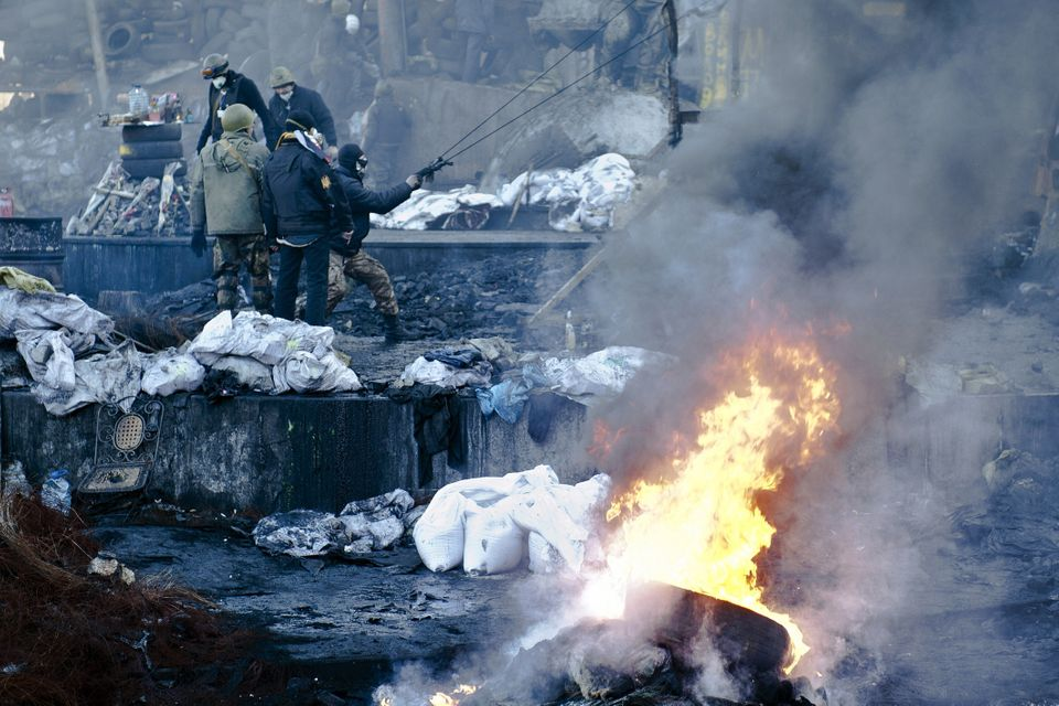Opposition demonstrators stand on a barricade during clashes with police in Kiev on February 18, 2014. (PIERO QUARANTA/AFP/Ge