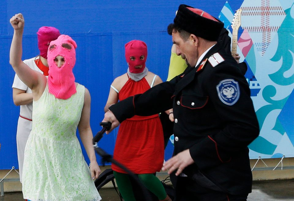 Members of the punk group Pussy Riot, including Nadezhda Tolokonnikova in the blue balaclava and Maria Alekhina in the pink b