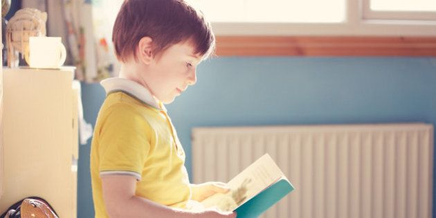 A young boy reading is his sun lit bedroom while sitting on a toy