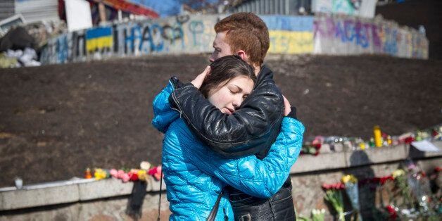 KIEV, UKRAINE - FEBRUARY 24: A young couple comfort each other beside floral tributes in Independence Square to the anti-gove