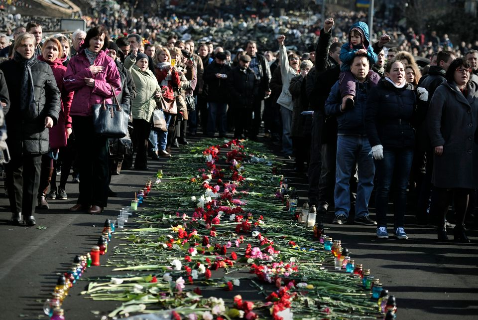 Ukrainians sing their national anthem by a huge line of flowers and candles leading to the barricades in central Kiev  on Feb