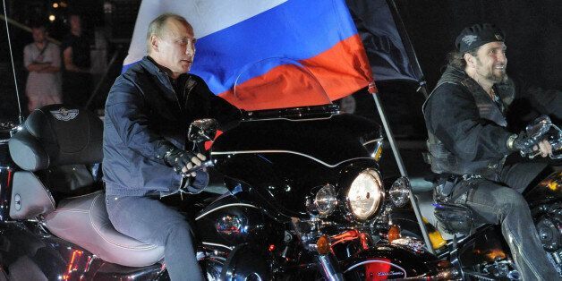 Russian Prime Minister Vladimir Putin (L) rides a motorbike as he takes part in the 16th annual motorbike festival held by 'T