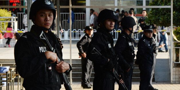 Chinese police stand guard at the scene of an attack at the main train station in Kunming, Yunnan province on March 2, 2014.
