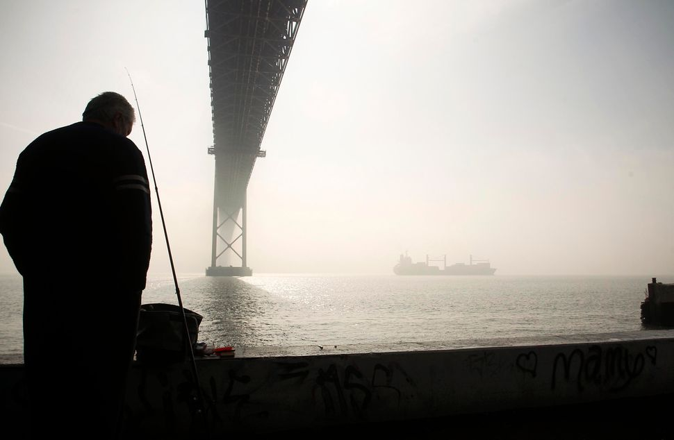 Arnaldo Cunha is silhouetted while fishing under the April 25th bridge as a cargo ship sails down the Tagus river shrouded in
