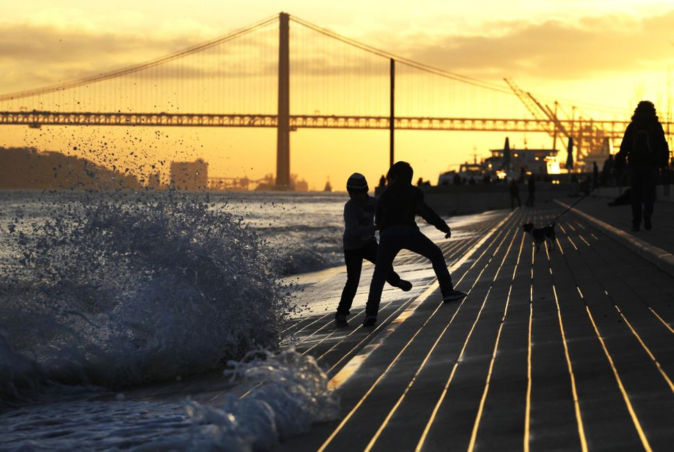 Young boys play with waves breaking at Tagus' Ribeira das Naus or Vessels Riverbank as the sun sets in Lisbon, Wednesday, Mar