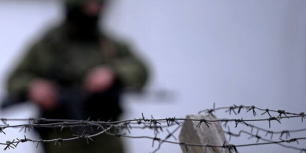 An armed man, believed to be a Russian serviceman, stands guard outside an Ukrainian military base in Perevalnoye on March 13