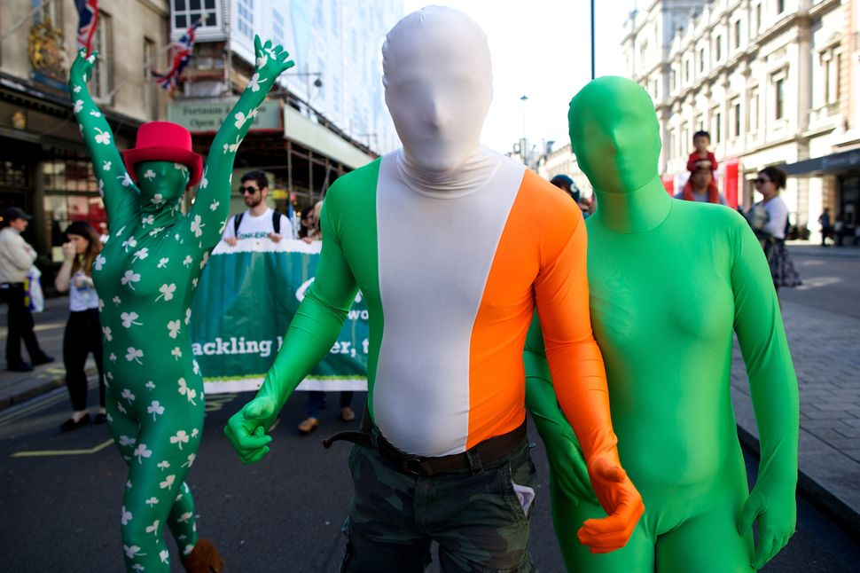 People dressed in Irish themed costumes take part in a St Patrick's Day parade in Central London on March 16, 2014. (ANDREW C