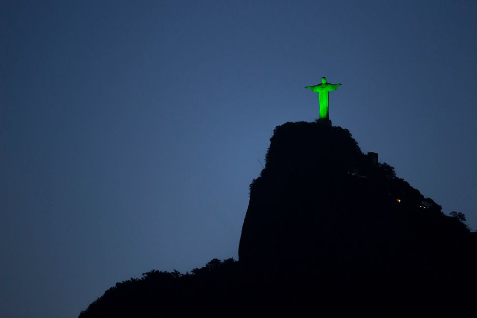 The Christ the Redeemer statue is illuminated in green in commemoration of St. Patrick's Day in Rio de Janeiro, Brazil, Monda