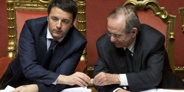 Premier Matteo Renzi, left, shares a biscuit with Economy Minister Pier Carlo Padoan as he attends a...