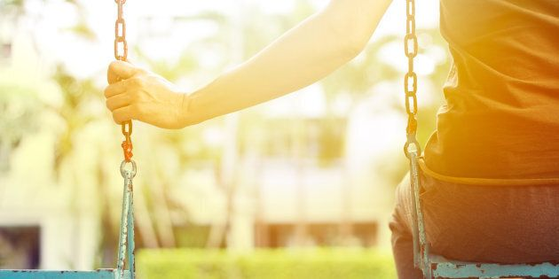 Lonely woman missing her boyfriend while swinging in the park villa in the