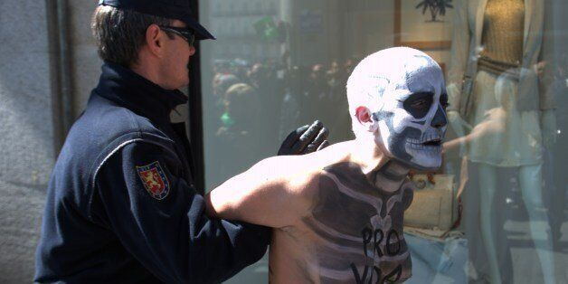 A police officer prevents a Femen activist disguised as a skeleton from staging a protest against an anti-abortion demonstrat